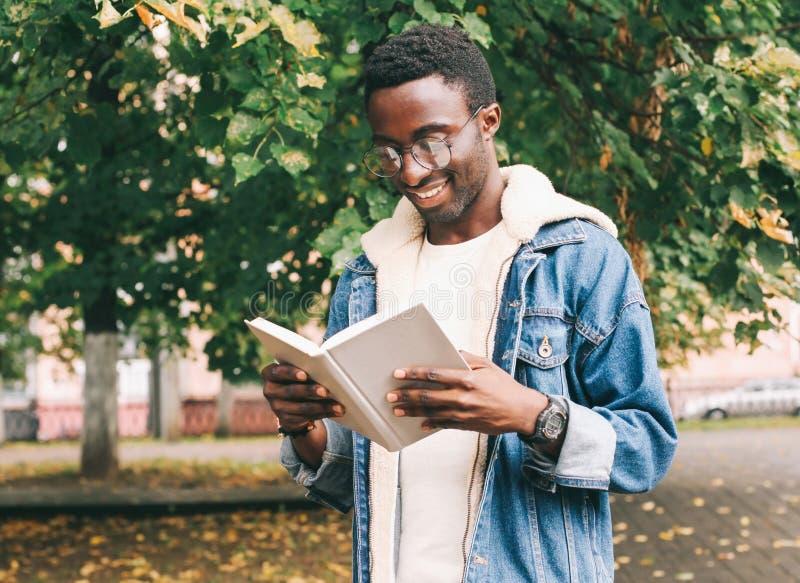 Szczęśliwego uśmiechniętego afrykańskiego mężczyzna czytelnicza książka w jesieni zdjęcie stock