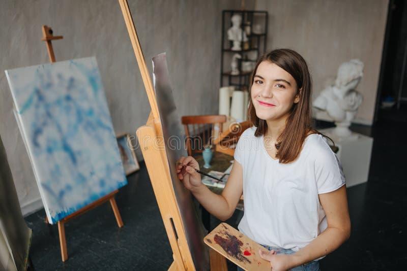 Szczęśliwego uśmiechniętego artysty malarza młoda piękna dziewczyna Pracujący tworzy proces Malować na sztaludze Inspirowana prac fotografia stock