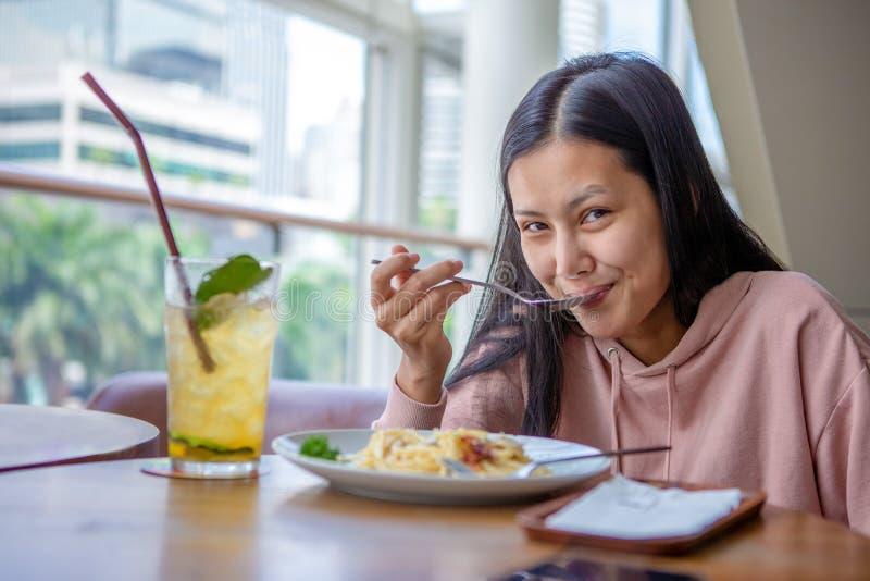 Szczęśliwego uśmiechniętego azjatykciego kobiety łasowania Włoski makaron z lemoniadą w restauracjach zdjęcie royalty free