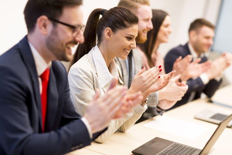 Szczęśliwego uśmiechniętego biznesu drużynowe klascze ręki podczas spotkania zdjęcie stock