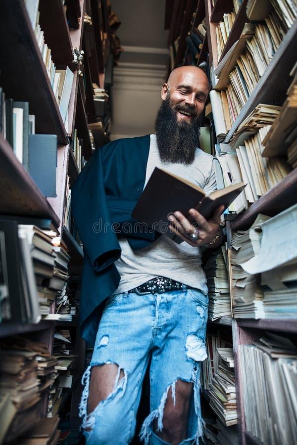 Szczęśliwego uśmiechniętego mężczyzna czytelnicza książka w półka na książki tle zdjęcie stock