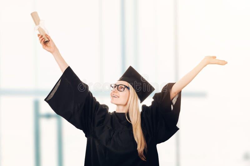 Szczęśliwego uniwersyteta magisterska jest ubranym nakrętka i toga zdjęcie royalty free