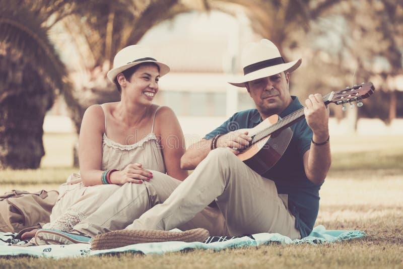 Szczęśliwego wieka średniego pary mężczyzny caucasian kobieta cieszy się plenerową czas wolny aktywność zostaje wpólnie gitarę ak zdjęcia royalty free