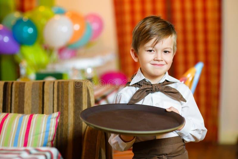 Szczęśliwej ślicznej chłopiec uśmiechnięty kelner trzyma a fotografia stock