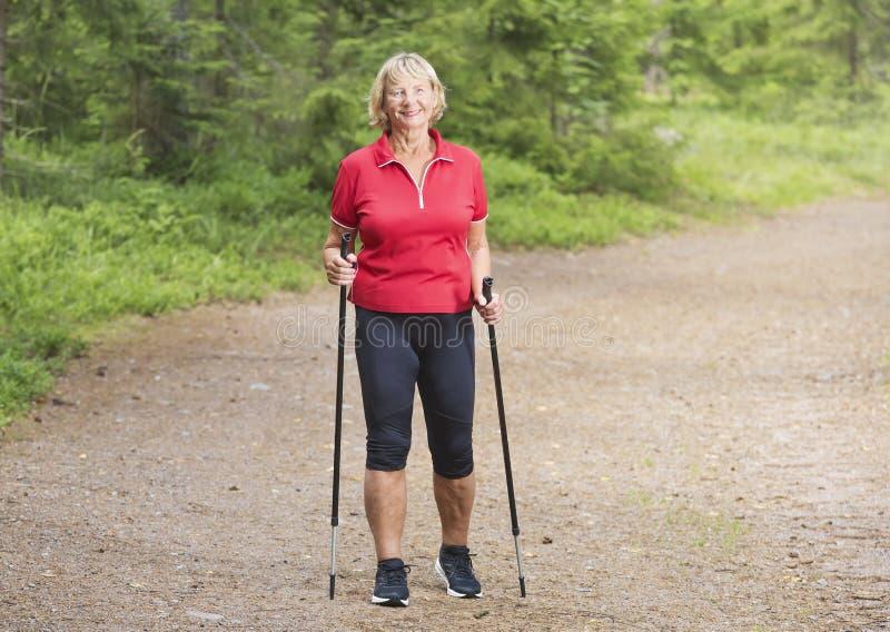 Szczęśliwej aktywnej starszej kobiety północny odprowadzenie w parku fotografia stock