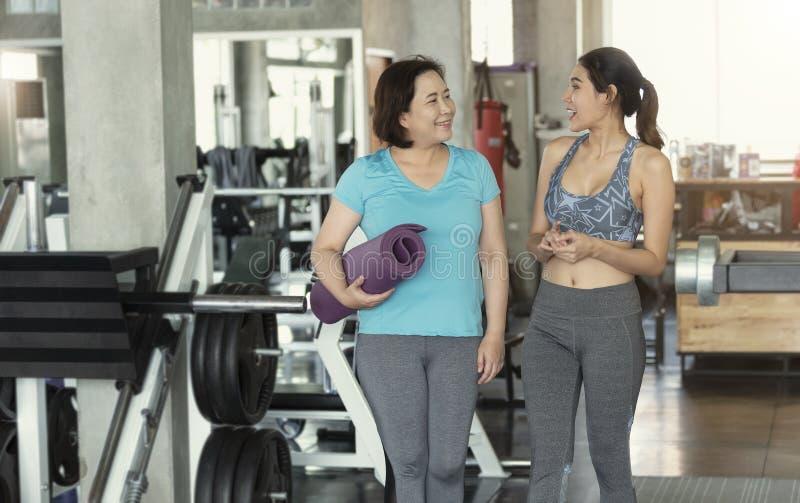 Szczęśliwej asyjki, pary starszej i młodej kobiety trzymającej maty jogi i chodzącej w sali fitness zdjęcia stock