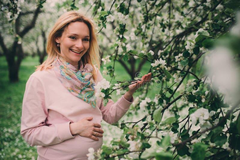 Szczęśliwej ciężarnej blondynki kobiety piękny chodzić plenerowy w wiosna ogródzie lub parku obraz stock