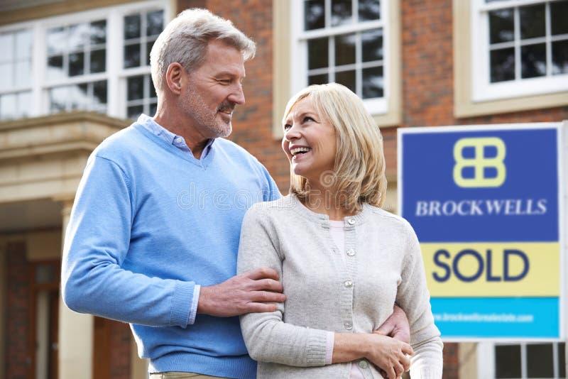 Szczęśliwej Dojrzałej pary Outside Trwanie dom Z Sprzedającym znakiem obrazy royalty free