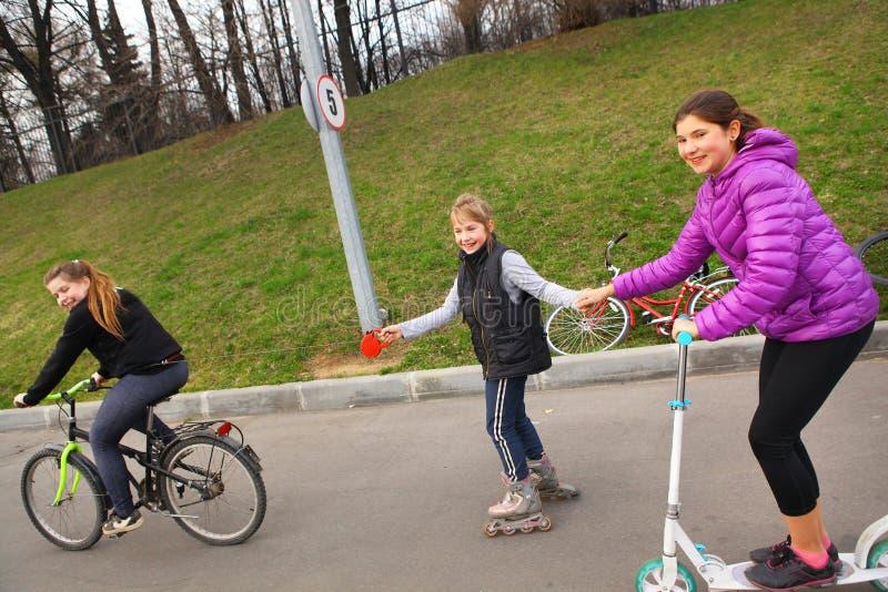 Szczęśliwej dziewczyna przyjaciela przejażdżki rolkowe łyżwy hulajnoga i bicykl na holowniczym fotografia stock