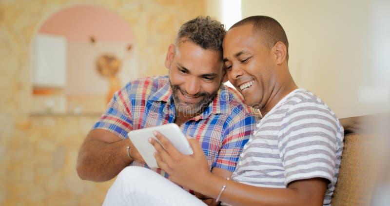 Szczęśliwej Homoseksualnej pary mężczyzna Używa pastylkę Homoseksualni ludzie zdjęcie royalty free
