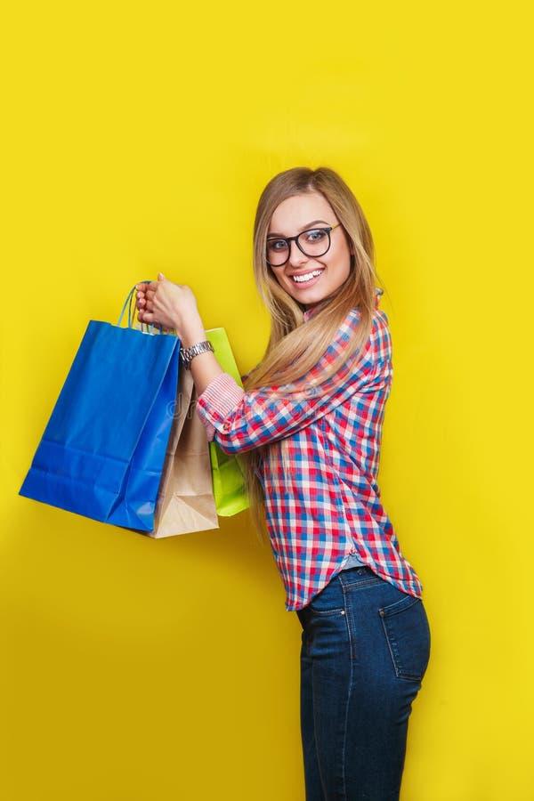 Szczęśliwej kobiety iść robić zakupy w ręce trzyma kolorowych pakunki obraz royalty free