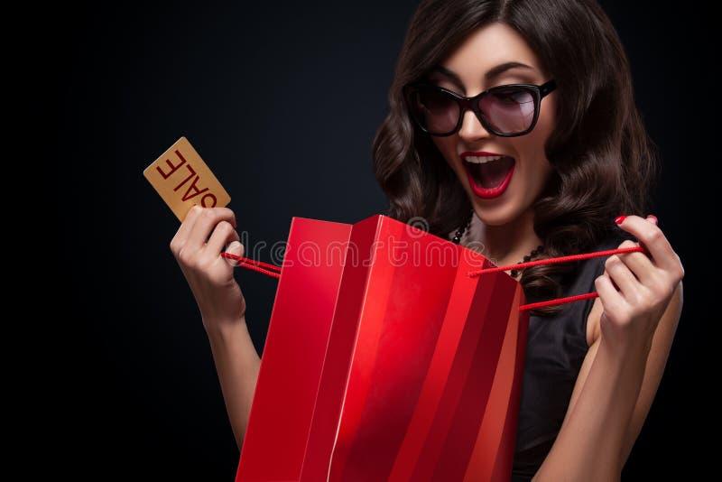 Szczęśliwej kobiety otwarta czerwona torba na ciemnym tle w czarnym Piątku wakacje obraz royalty free