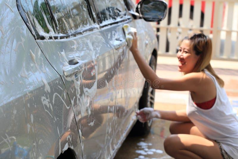 Szczęśliwej kobiety płuczkowy samochód obraz royalty free