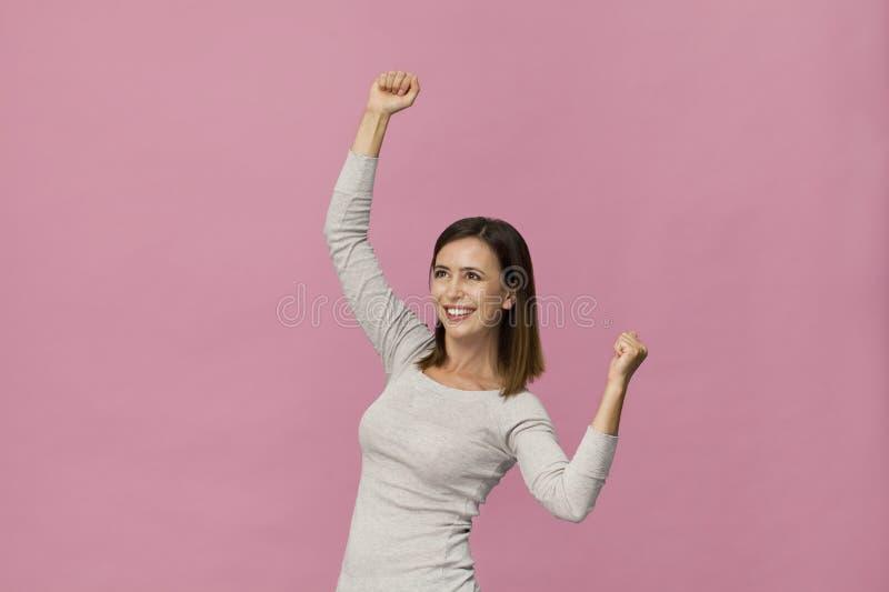 Szczęśliwej młodej brunetki kobiety portreta zwycięstwa uśmiechnięty gest przeciw różowemu tłu obrazy royalty free