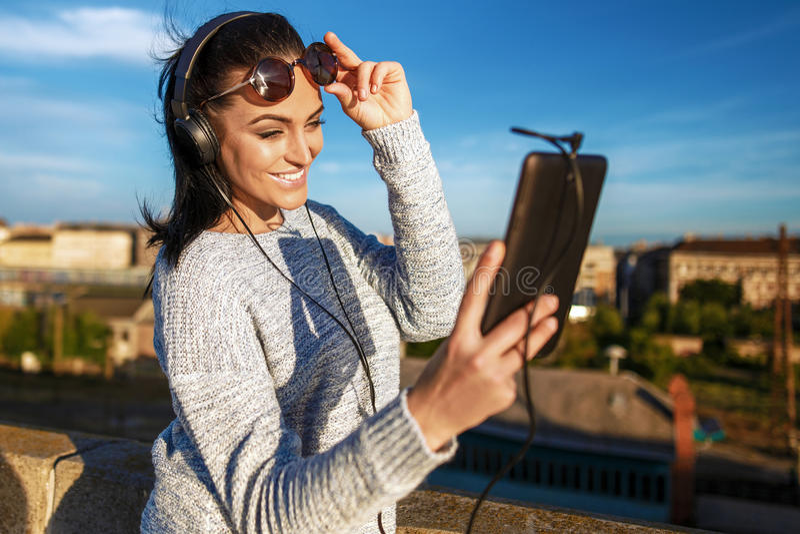 Szczęśliwej młodej kobiety słuchająca muzyka na pastylce w mieście plenerowym zdjęcia stock