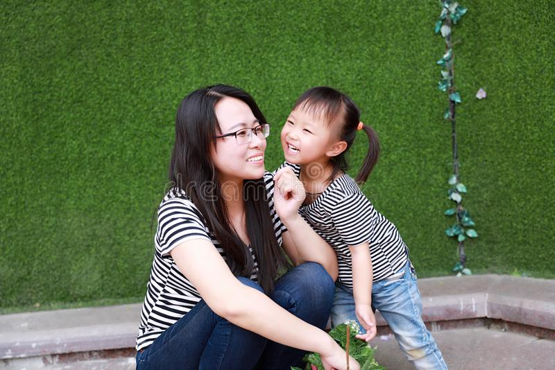 Szczęśliwej małej ślicznej uroczej dziewczynki dziecka Chiński buziak i zabawę z macierzystą mamą przy lato parka natury szczęści fotografia stock