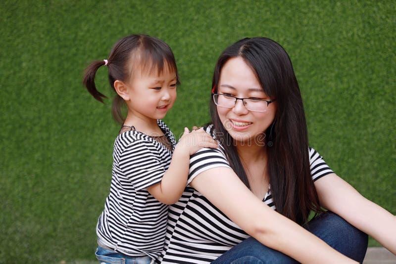 Szczęśliwej małej ślicznej uroczej dziewczynki dziecka uśmiechu Chiński śmiech zabawę z macierzystą mamą przy lato parka natury s zdjęcia stock