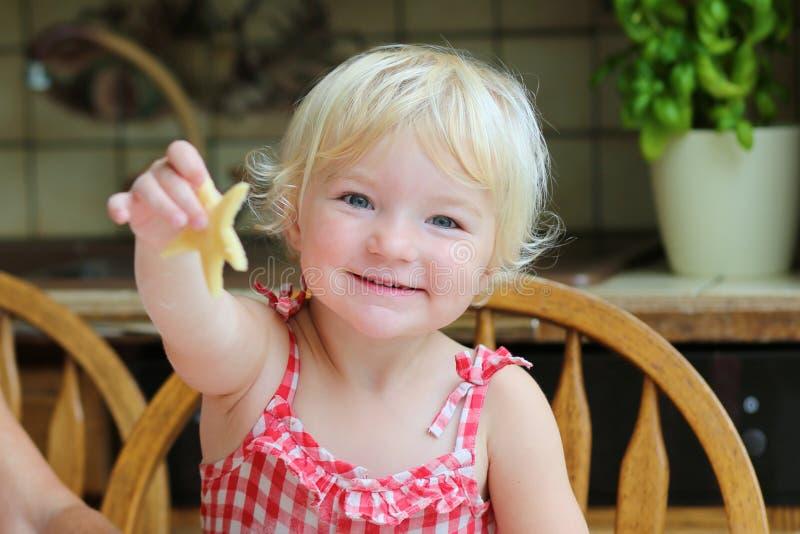 Szczęśliwej małej dziewczynki wypiekowi ciastka w kuchni obraz royalty free