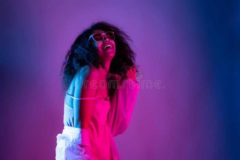 Szczęśliwej mody dziewczyny odzieży szkieł młody afrykański deszczowiec śmia się na purpury ścianie zdjęcie royalty free