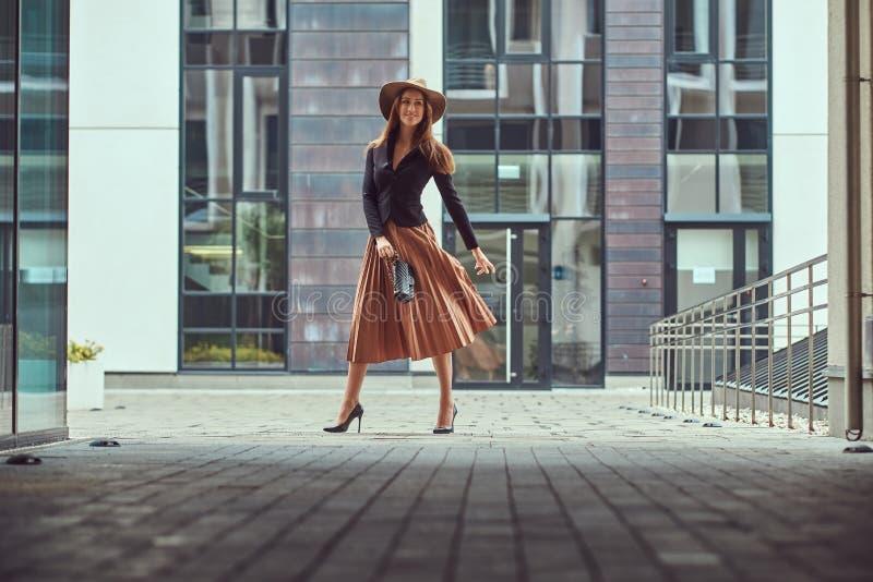 Szczęśliwej mody elegancka kobieta jest ubranym czarną kurtkę, brown kapelusz i spódnica z torebką, trzymamy mocno odprowadzenie  zdjęcie royalty free