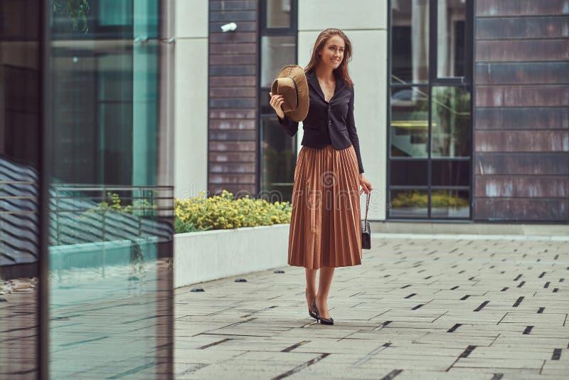 Szczęśliwej mody elegancka kobieta jest ubranym czarną kurtkę, brown kapelusz i spódnica z torebką, trzymamy mocno odprowadzenie  fotografia royalty free