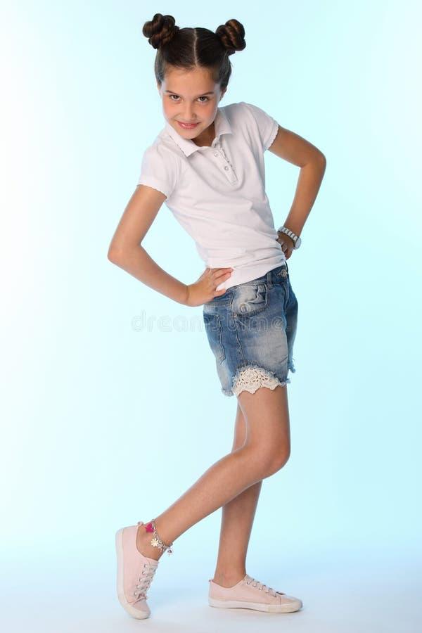 Szczęśliwej nikłej dziecko dziewczyny pełny przyrost w drelichów skrótach z nagimi nogami fotografia stock