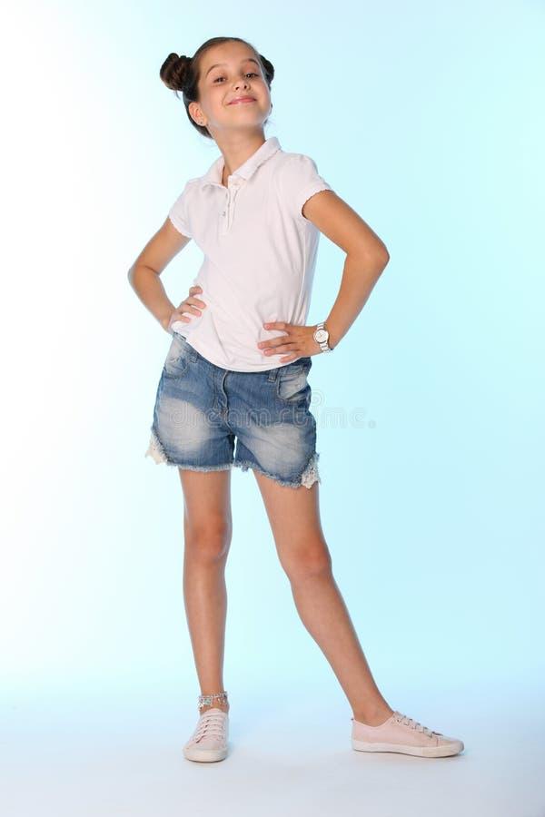 Szczęśliwej nikłej dziecko dziewczyny pełny przyrost w drelichów skrótach z nagimi nogami obrazy stock