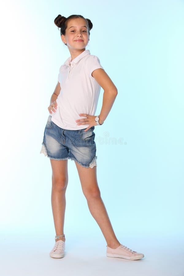 Szczęśliwej nikłej dziecko dziewczyny pełny przyrost w drelichów skrótach z nagimi nogami obraz stock