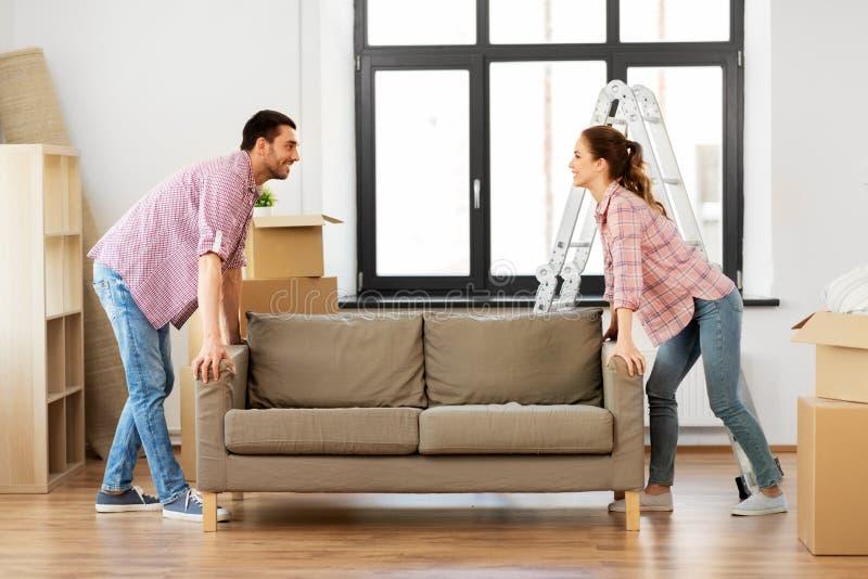 Szczęśliwej pary poruszająca kanapa przy nowym domem zdjęcie stock
