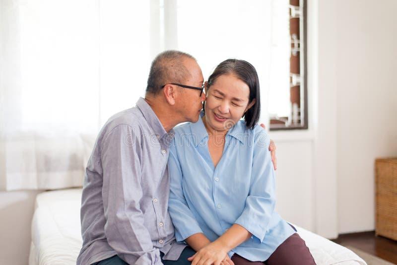 Szczęśliwej pary starszy azjatykci buziak policzek wpólnie na łóżku w domu obraz stock