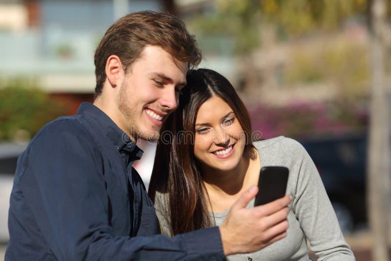 Szczęśliwej pary telefonu ordynacyjna zawartość w parku obraz stock