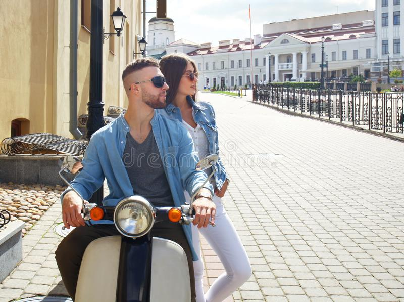 Szczęśliwej potomstwo pary jeździecka hulajnoga w miasteczku Przystojna faceta i młodej kobiety podróż Przygody i wakacji pojęcie zdjęcie stock