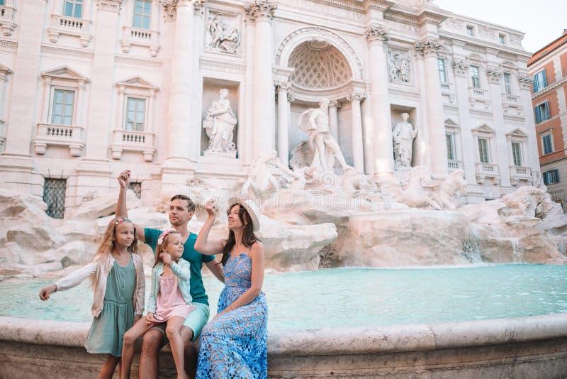 Szczęśliwej rodziny trowing monety przy Trevi fontanną, Rzym szczęście, na dobre Małe dziewczynki i rodzice robi życzeniu wracali zdjęcia stock