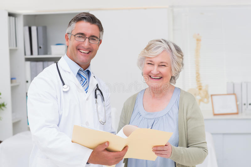 Szczęśliwej samiec doktorski i żeński pacjent z raportami fotografia royalty free
