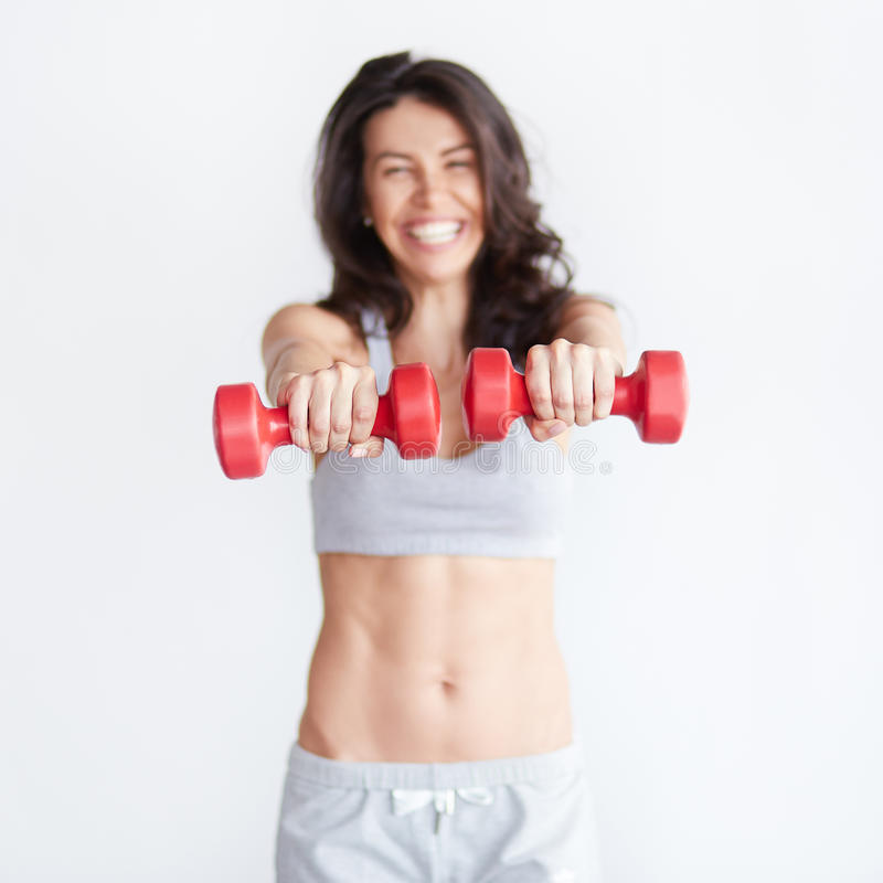 Szczęśliwej sprawności fizycznej kobiety dumbbells podnośny ono uśmiecha się rozochocony zdjęcia stock