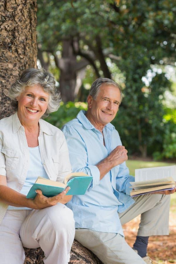 Szczęśliwej starej pary czytelnicze książki wpólnie siedzi na drzewnym bagażniku fotografia stock