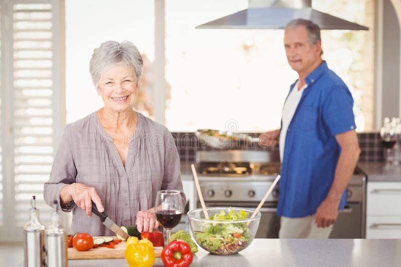 Szczęśliwej starszej kobiety tnący warzywa z mężem w tle fotografia stock