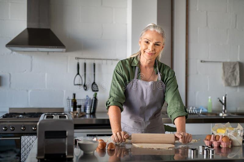Szczęśliwej starszej kobiety toczny ciasto fotografia royalty free