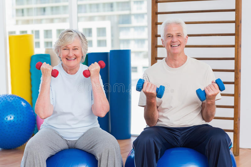 Szczęśliwej starszej pary podnośni dumbbells na ćwiczenie piłce zdjęcia royalty free