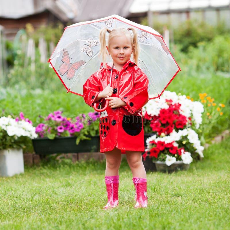 Szczęśliwej zabawy ładna mała dziewczynka w czerwonym deszczowu z parasolowym odprowadzeniem w parkowym lecie zdjęcia royalty free
