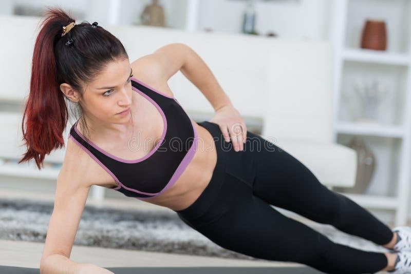 Szczęśliwej zdrowej kobiety sprawności fizycznej ćwiczy dom obraz royalty free