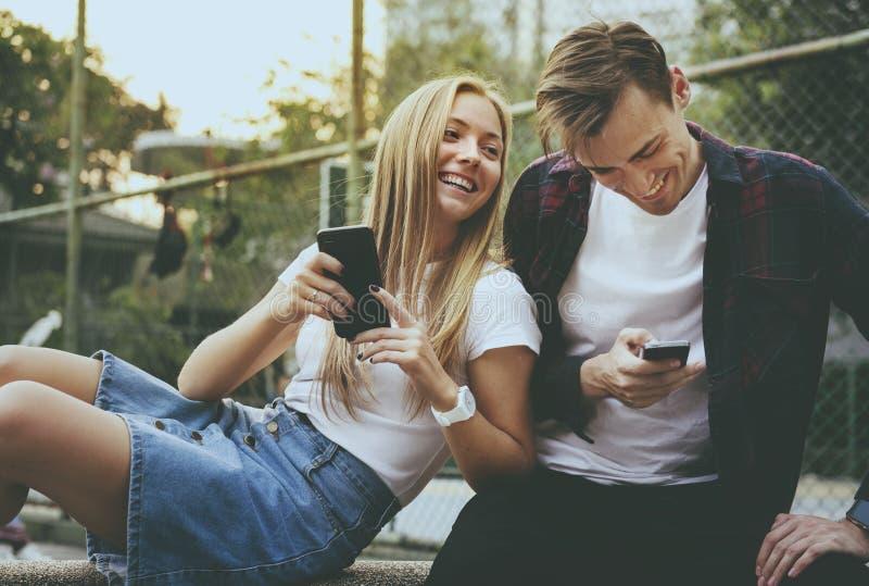 Szczęśliwi śliczni potomstwa dobierają się w parku używać smartphones wpólnie zdjęcie royalty free