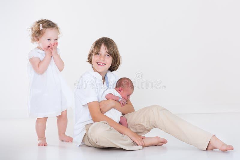 Szczęśliwi śmia się dzieciaki w białym pokoju z biel ubraniami fotografia royalty free
