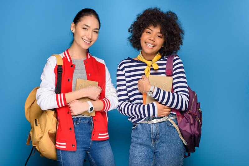 szczęśliwi żeńscy amerykanin afrykańskiego pochodzenia i azjaty ucznie pozuje z książkami zdjęcia stock