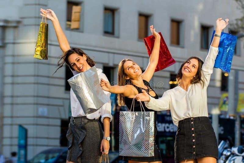 Szczęśliwi żeńscy kupujący trzyma torby w powietrzu obrazy stock