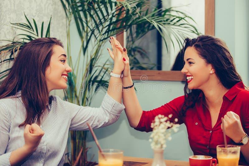 Szczęśliwi żeńscy przyjaciele dają wysokości, świętuje sukces podczas gdy patrzejący each inny fotografia royalty free