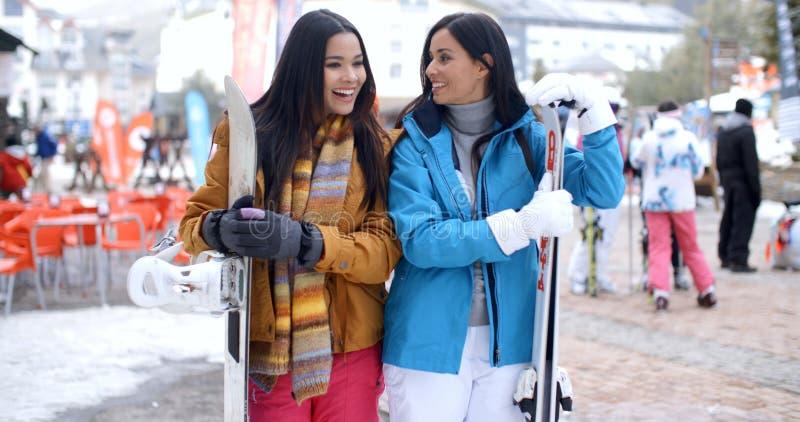 Szczęśliwi żeńscy przyjaciele przy zima ośrodkiem narciarskim obrazy stock