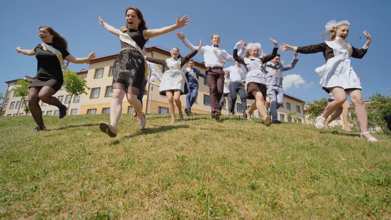 Szczęśliwi absolwenci rosjanin szkoła pojawiać się od wzgórza i biegają w kierunku szczęścia za obraz stock