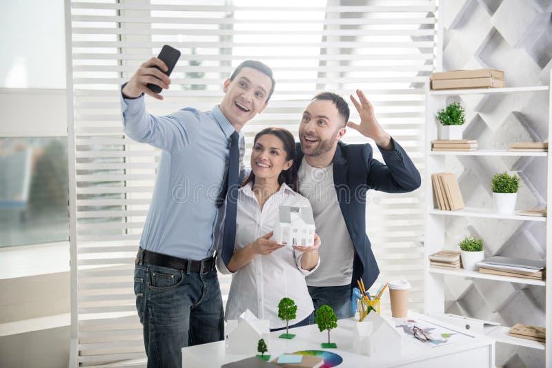 Szczęśliwi architekci bierze selfies w biurze zdjęcie royalty free