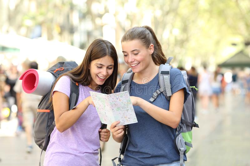 Szcz??liwi backpackers konsultuje papierowego przewdonika w ulicie fotografia stock